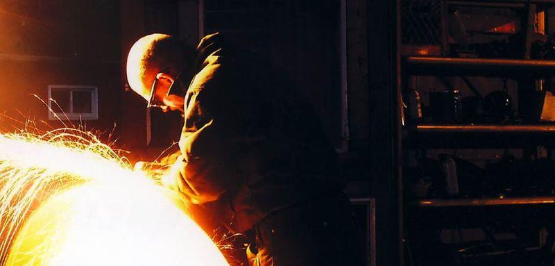 Artist John T. Unger cutting firebowl