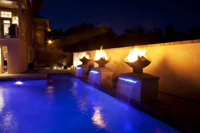 Sculptural Firebowls lighting pool at night
